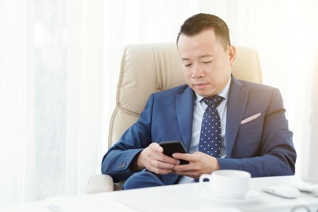 彼のオフィスのアームチェアで起業家テキストメッセージのミディアムショット 無料写真
