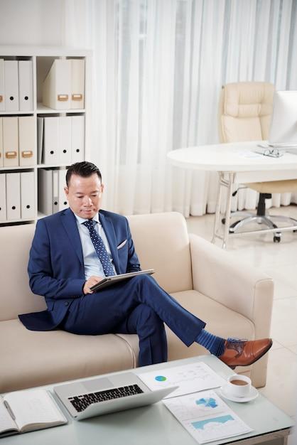 デジタルタブレットでソファに座っている起業家の完全な長さのショット 無料写真