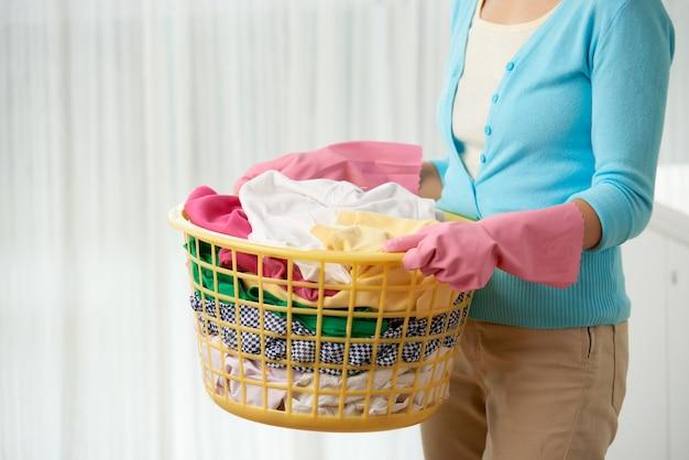 リネンバスケットを持って洗濯をしている認識できない女性をトリミング 無料写真