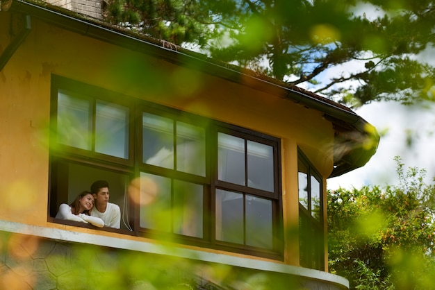 Длинный выстрел пара смотрит в окно своего нового дома Бесплатные Фотографии