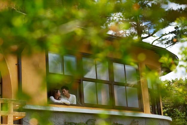 マンションのテラスで寄り添うカップルのロングショット 無料写真