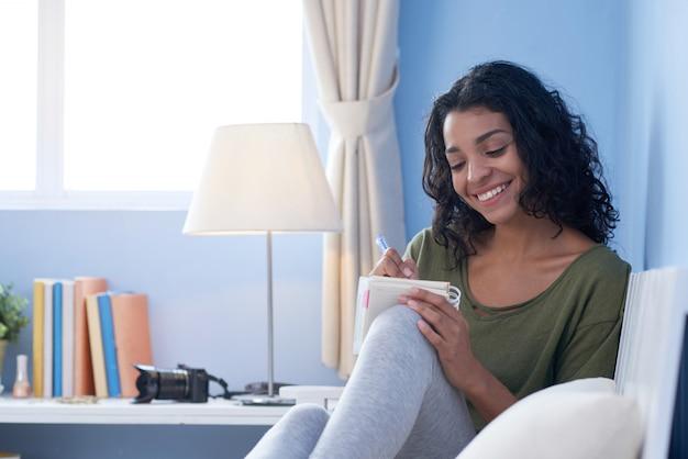 彼女の部屋のソファで何気なく休んでノートを作る若い女の子のミディアムショット 無料写真