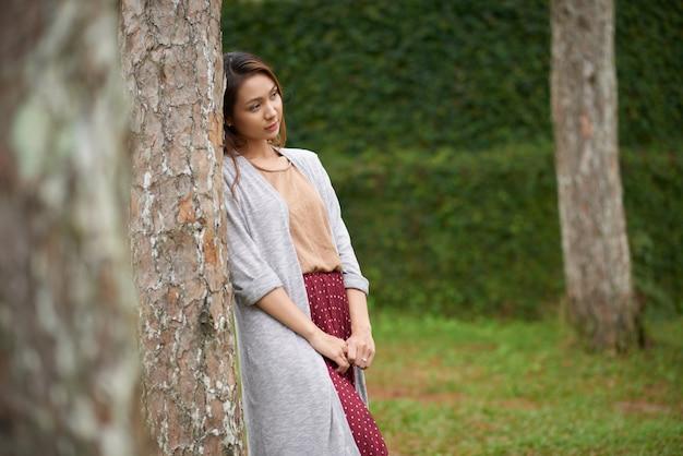 木にもたれて、カメラから離れて見て美しい女性の側面図 無料写真