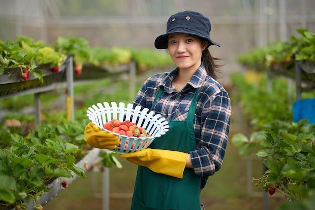 熟したイチゴのバスケットを持って全体的に農家の若いアジア女性のミディアムショット 無料写真