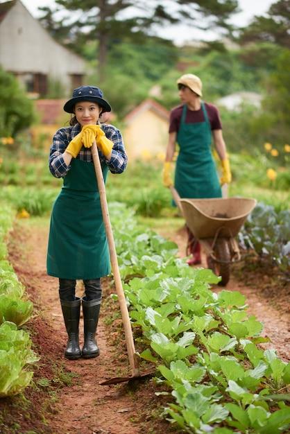Портрет молодого фермера с копать мотыгой, глядя на камеру со своим коллегой, толкая вагон на заднем плане Бесплатные Фотографии