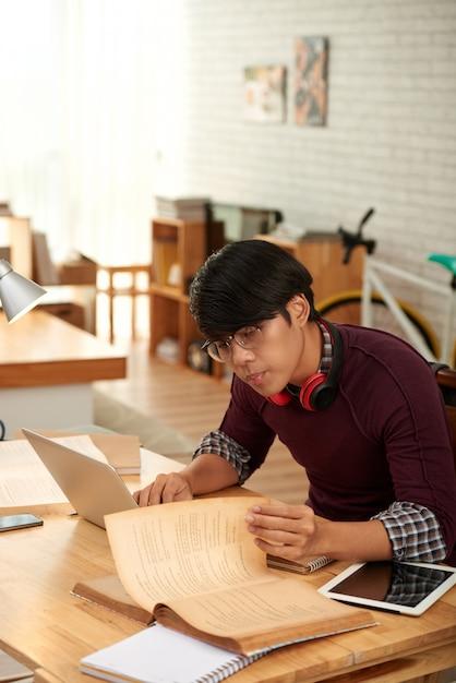 インテリジェントな学生が彼のテーブルで本を読んで情報を見つける 無料写真