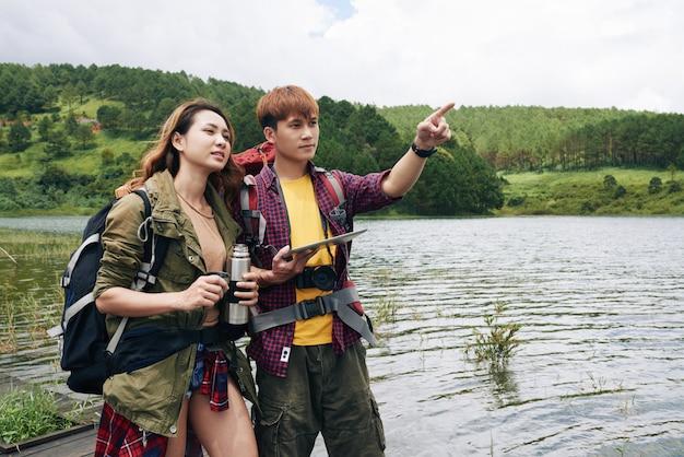 山の方向のデジタルタブレットの地図を使用してアジアの若いカップル 無料写真