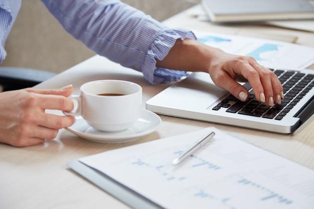 ノートパソコンでキーボードとお茶のカップを保持している実業家の手のクローズアップ 無料写真