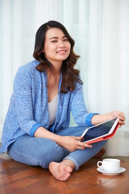 コーヒーを飲みながらデジタルタブレットを持つ女性 無料写真