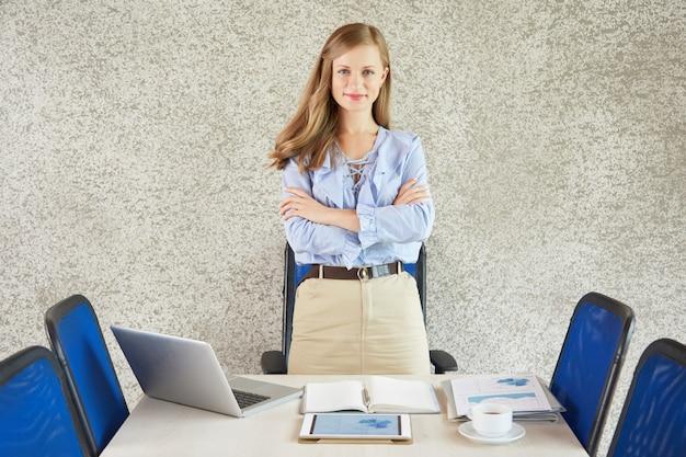 Портрет успешной бизнес-леди, стоя за столом со сложенными руками Бесплатные Фотографии