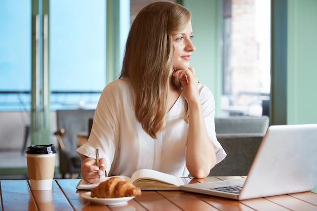 Молодая женщина, сидя за столом, держа перо и глядя в окно Бесплатные Фотографии