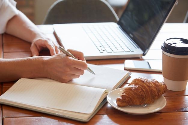Крупным планом стол для завтрака с женскими руками, положив информацию для ежедневника Бесплатные Фотографии