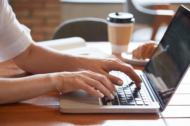 Крупным планом женских рук, набрав на ноутбуке с вынос чашки и круассан Бесплатные Фотографии