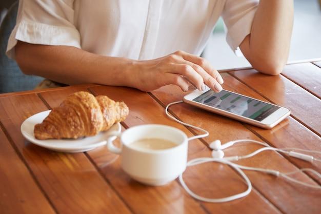 Крупным планом женских рук, отправив сообщение на смартфоне, имея утренний кофе Бесплатные Фотографии