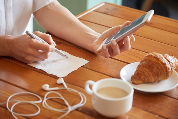 ナプキンにメモを書く女性の手のクローズアップ 無料写真