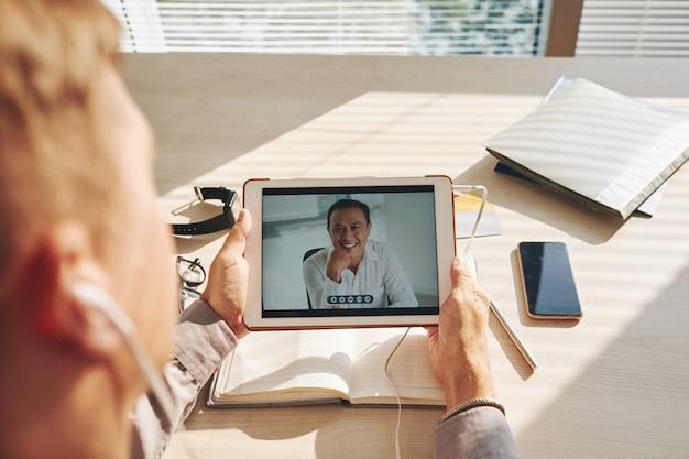 認識できない男の机に座って、タブレットでビデオ通話 無料写真