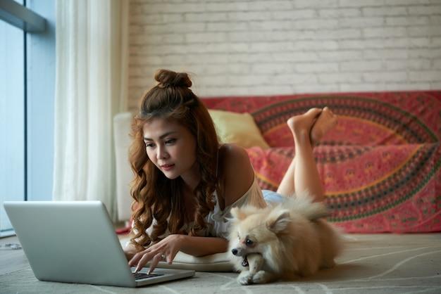 横にある小さなペットの犬とのラップトップで家の床に横たわって若いアジア女性 無料写真