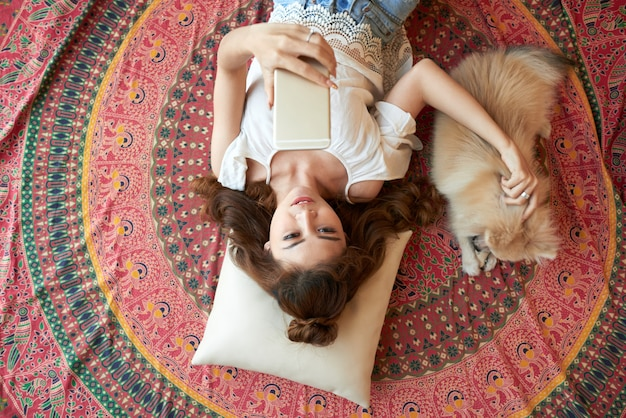 スマートフォンで自宅の床に横たわって、小さな犬をかわいがる若いアジア女性 無料写真