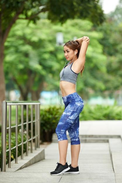 スポーツトップと公園で腕のストレッチをしているレギンスの若いアジア女性 無料写真