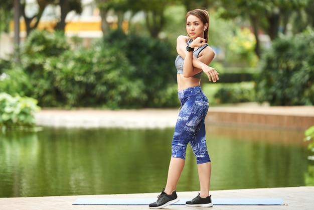 都市公園の池のそばに立って、腕のストレッチを行う運動のアジア女性 無料写真