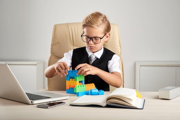 Молодой белокурый кавказский мальчик сидя в исполнительном стуле в офисе и играя с строительными блоками Бесплатные Фотографии
