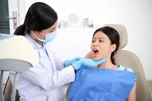 口を開けて、彼女の歯を見て歯科医と椅子に座っているアジアの女性患者 無料写真
