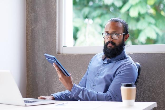 インド人のオフィスの机に座って、タブレットを使用して 無料写真