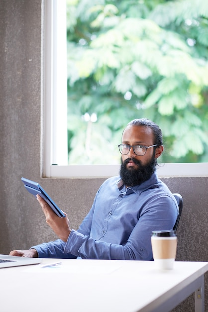 Индийский мужчина сидел на столе в офисе с планшета и, глядя на камеру Бесплатные Фотографии