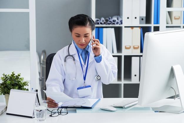 Азиатский женский доктор сидя на столе в офисе и вызывая на мобильном телефоне Бесплатные Фотографии