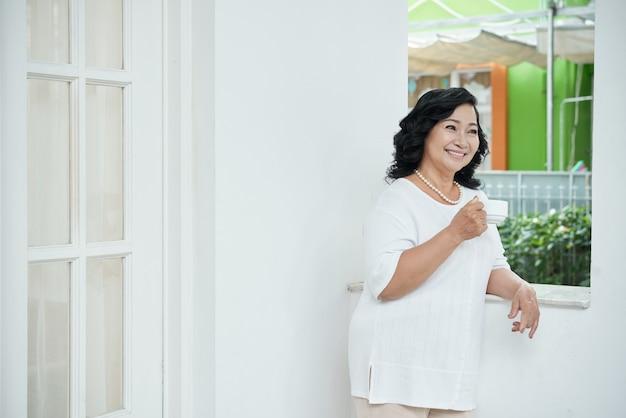 自宅のバルコニーにもたれて、お茶のカップを保持している幸せの上級アジアの女性 無料写真