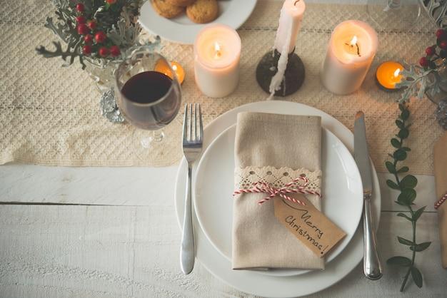 Тарелки, столовые приборы, салфетка и бокал вина на рождественский ужин на столе со свечами Бесплатные Фотографии