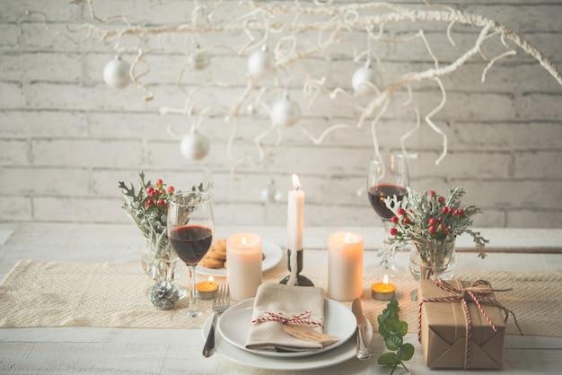 クリスマスディナーのテーブルに配置されたプレゼント、プレート、カトラリー、キャンドル、装飾品 無料写真
