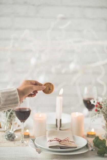 クリスマスディナーテーブルの上にクッキーを保持している認識できない女性の手 無料写真