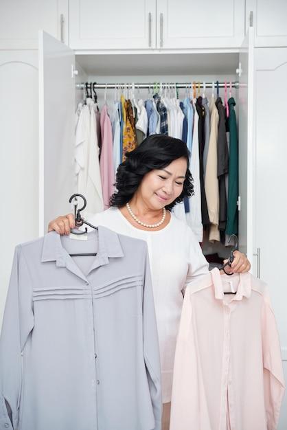 自宅で開いているワードローブの前に立って、ハンガーにブラウスを保持しているシニアアジア女性 無料写真
