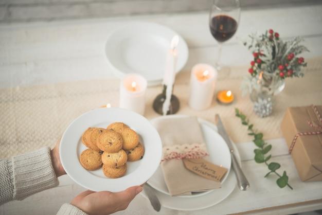 Руки до неузнаваемости женщины положить тарелку печенья на прекрасный рождественский стол Бесплатные Фотографии