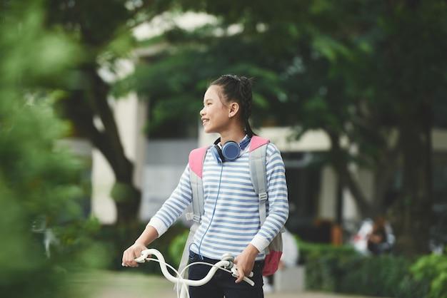 自転車を押しながら公園で周りを見て幸せなアジアの女の子 無料写真