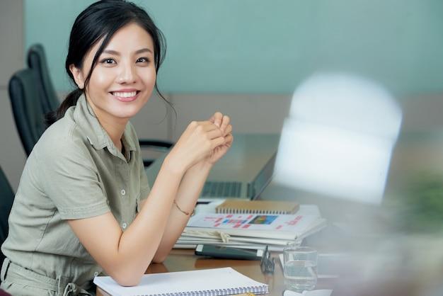 Довольно бизнес-леди позирует на ее рабочий стол, улыбка на камеру Бесплатные Фотографии