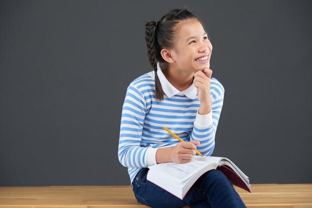 Средний снимок азиатской школьницы, наслаждаясь домашнее задание Бесплатные Фотографии