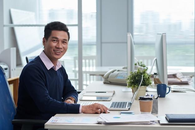 オフィスの机に座って、カメラ目線のベトナム人実業家の笑みを浮かべてください。 無料写真