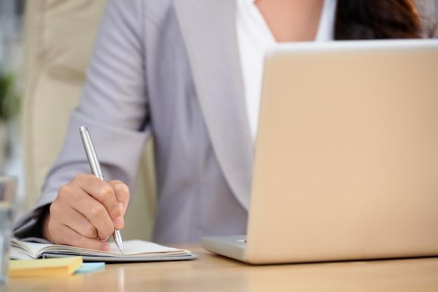Средняя часть обрезанной женщины, копирующей важные данные с ноутбука Бесплатные Фотографии