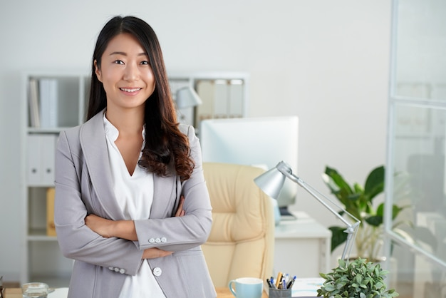 組んだ腕を持つオフィスでポーズをとって陽気な韓国ビジネス女性 無料写真