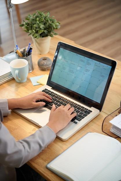 Высокий угол обзора обрезанного человека, заполняющего онлайн календарь Бесплатные Фотографии