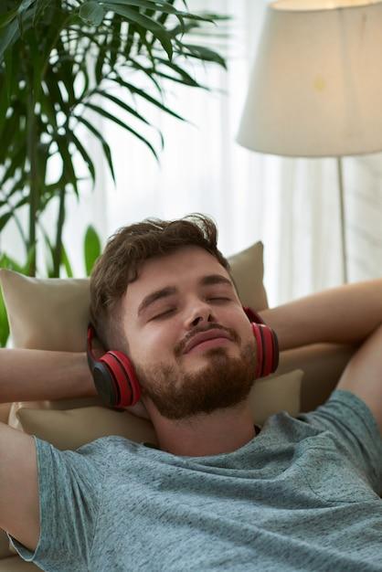Крупным планом человека, наслаждаясь музыкой, лежа на диване руки за голову Бесплатные Фотографии