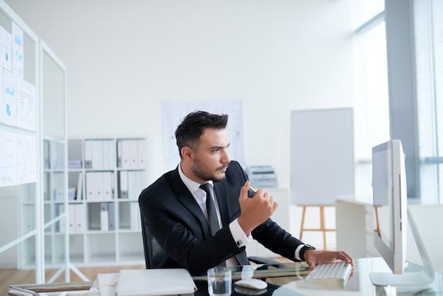 オフィスに座っていると、コンピューターの画面を見ているスーツの若い白人実業家 無料写真
