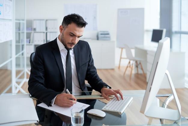 オフィスで座っている、コンピューターで作業し、紙に書くビジネススーツの白人男性 無料写真