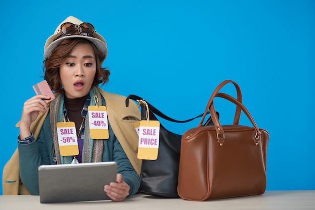 Азиатская женщина, одетая в новую одежду со скидкой этикетки, сидя с планшета и кредитной карты Бесплатные Фотографии