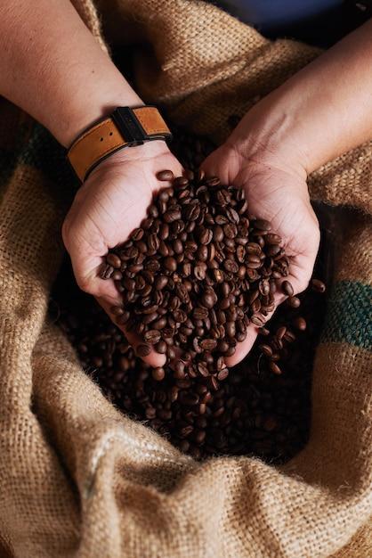 Руки до неузнаваемости мужчина держит горсть кофейных зерен из мешковины Бесплатные Фотографии