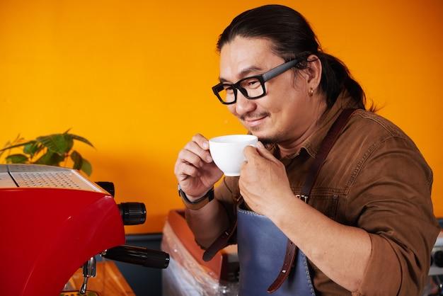 Азиатский мужчина в фартуке стоит рядом с кофемашиной, держит чашку и пахнет кофе Бесплатные Фотографии