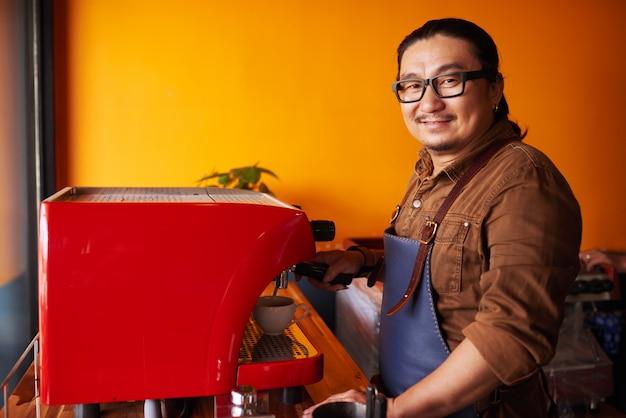 エスプレッソマシンの横に立っていると笑顔のエプロンで中年のアジア人の笑顔 無料写真
