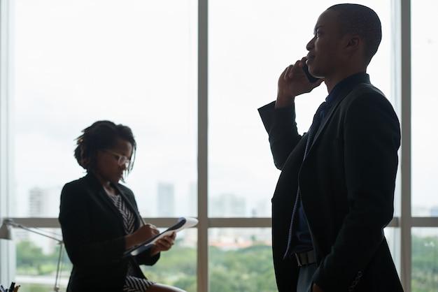 Деловые люди разговаривают по телефону и пишут в тетради против окна офиса Бесплатные Фотографии